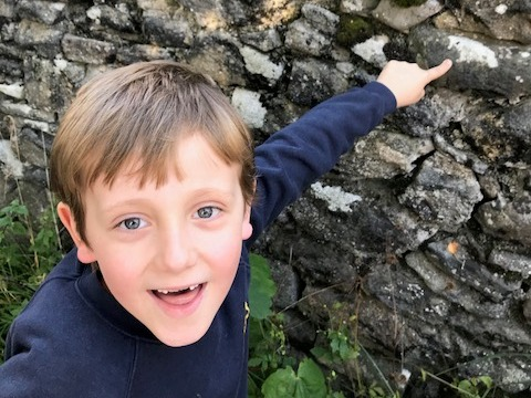 Boy pointing to lichen